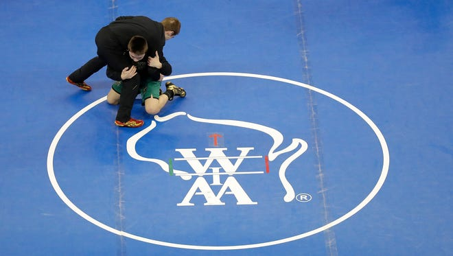 Contestants warm up on the mats prior to the 2018 State Individual Wrestling Tournament Finals Saturday, February 24, 2018 at the Kohl Center in Madison, Wis.
