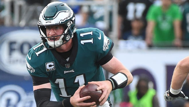 Philadelphia Eagles quarterback Carson Wentz (11) breaks a tackle by Los Angeles Rams defensive end Morgan Fox (97) for a gain in the second half of the game at the Los Angeles Memorial Coliseum.