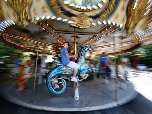 Maggie Pecus, of Wauwatosa, Wisconsin, rides a Merry-Go-Round