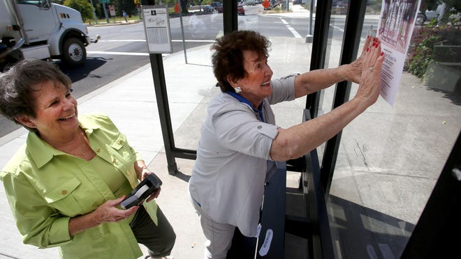 Lorraine Dye, left, and Britta Franz place a flyer on a Cherriots bus shelter in front of Magoos Sports Bar. The two are organizing an event to have art displayed on Cherriots bus stops in the area.
