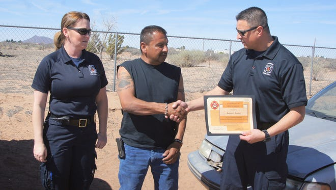 Ramon Pena, center, of Ramon's Towing, provided 16 vehicles for Deming Fire Department firefighter/EMTs to train in emergency extricating procedures. Pena was presented a certificate for his donations by DFD Chief Raul Mercado and Battalion Chief Heather Sosa.