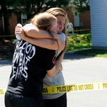 Two women embrace across police tape at the scene of a shooting on the 600 block of Glenbrook Drive in Newark. Two white male victims were shot and flown to Columbus hospitals.