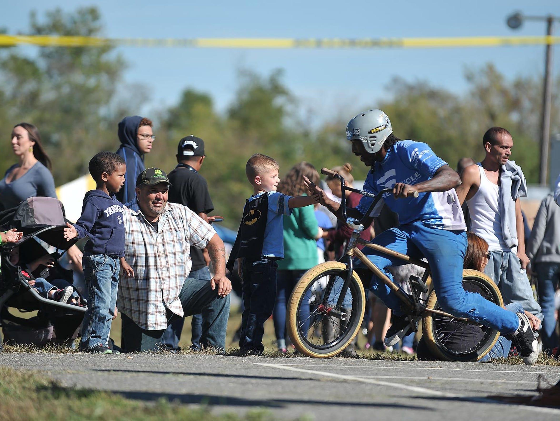 A BMX rider gives a high five to Keagan Santana, 4,
