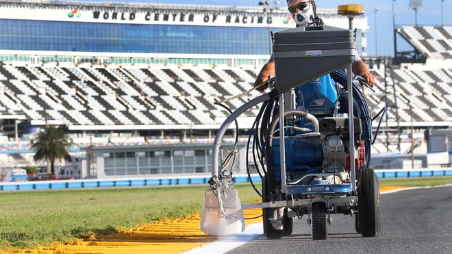 Operations worker Daniel Laird lines the road shoulder as preparation continues for the coming week's NASCAR events on the road course at Daytona International Speedway.