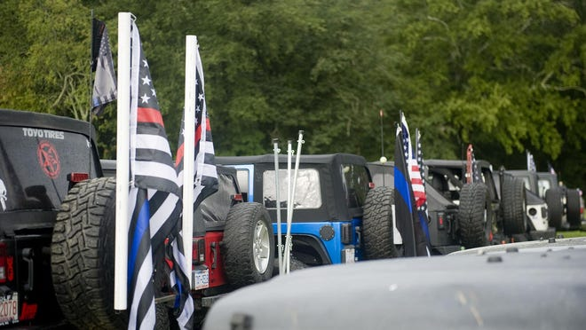 """Members of the Hendersonville Jeep Club park their Jeeps, many adorned with American flags, """"Thin Blue Line"""" flags and """"Honor the 4"""" flags, prior to the club's """"Patriot Parade"""" caravan through Henderson County and Transylvania County Saturday morning, from Mills River Brewing Co., in honor of local service men and women."""