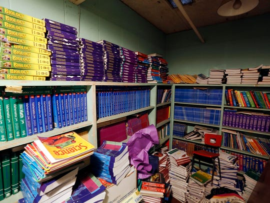 In this Oct. 23, 2014 photograph, old textbooks that Durant education officials say they can't use because they don't line up with new Common Core State Standards, are kept in a storage closet at the Durant, Miss., complex. By not having a book to send home with every student in every subject, Durant is violating state law. Officials say that just buying books for grades K-3 would cost $34,000, the same amount that's needed to repair a leaking roof. (AP Photo/Rogelio V. Solis)