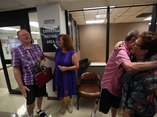 Lee Bennett Hopkins and longtime partner Charles Egita (left) got married in 2014. In this photo, Hopkins hugs Arlene Goldberg, a local LGBT marriage activist, after receiving a marriage license from the Lee County Clerk of Courts.