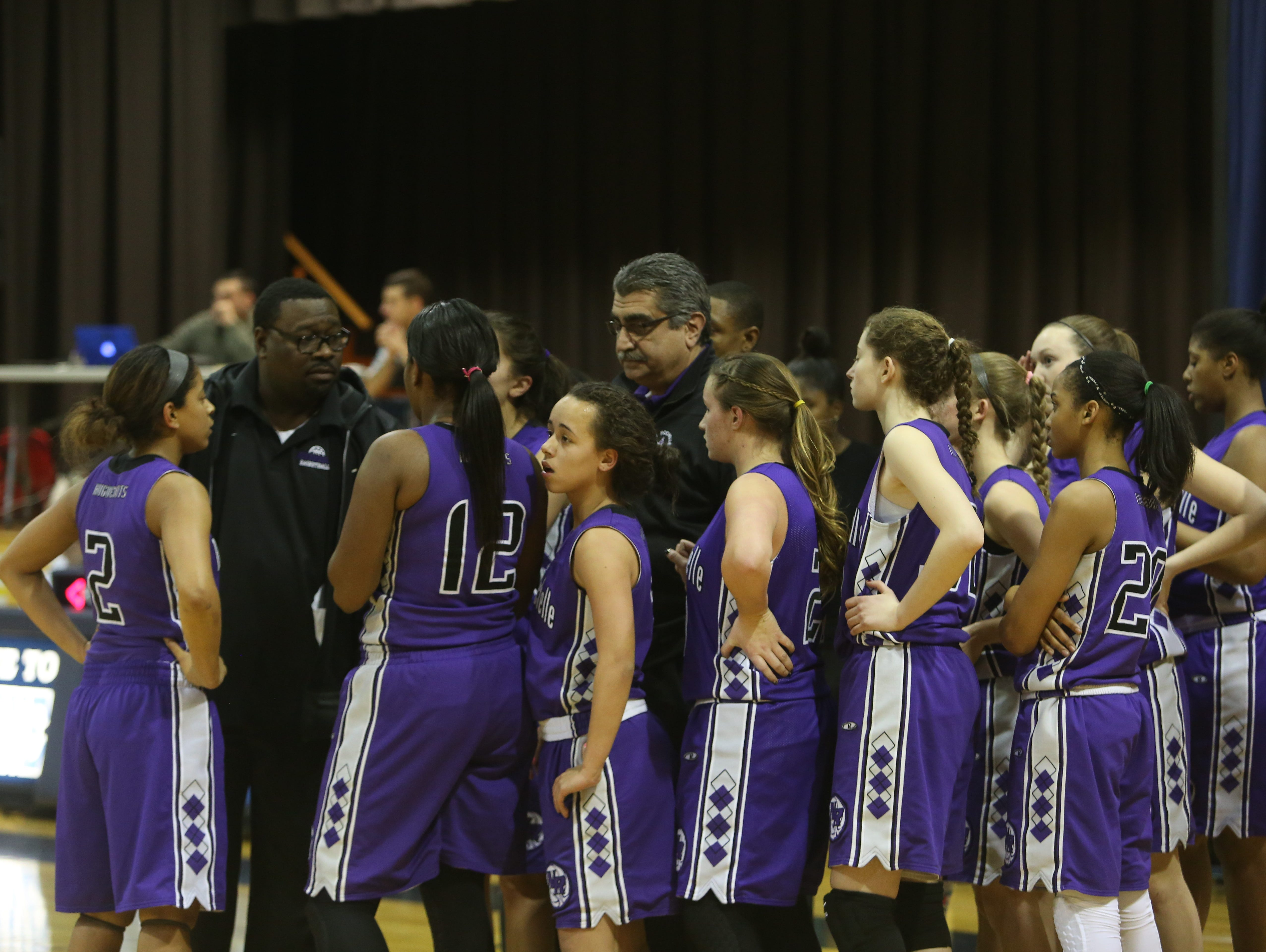 New Rochelle coach Bob Bynum (second from left) talks to the team during a girls basketball game at Ursuline High School in New Rochelle Jan. 21, 2015.