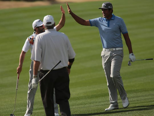 Tony Finau, right, high fives Adam Hadwin after he hits a birdie on18 on the Nicklaus Private Course during the second round of the Humana Challenge on Friday, January 23, 2015 in La Quinta.