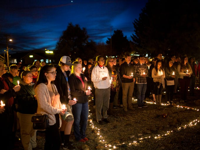 Members of the community gather at a candlelight vigil