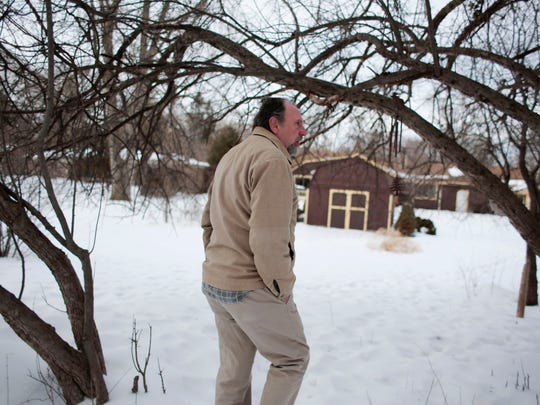 Rick Shriner looks at the deer tracks crossing his