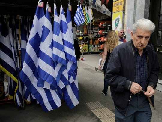 An man walk past a kiosk with Greek flags for sale