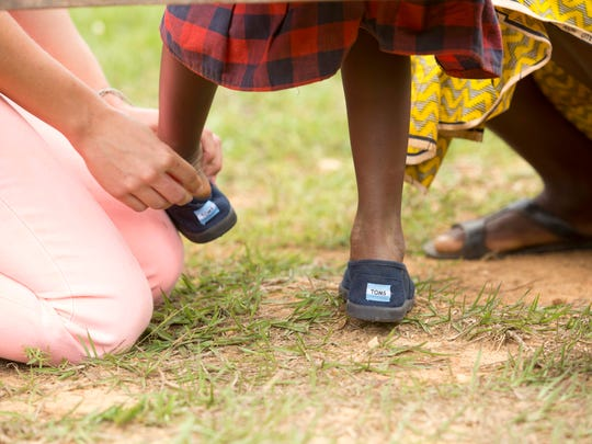 A child in Rwanda gets a free pair of Toms shoes, one