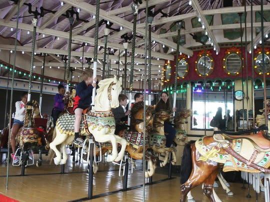People enjoy a ride on the Grand Carousel during opening day of Playland in Rye May 9, 2015.