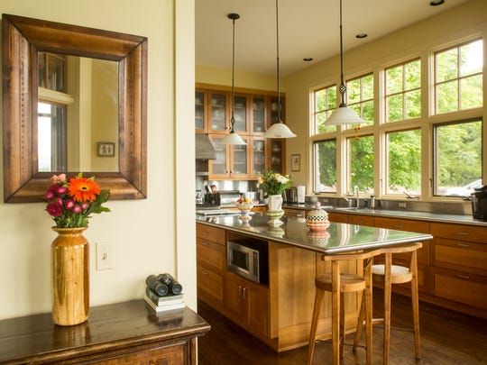 Contemporary cherry cabinets complement the stainless steel island in the kitchen.