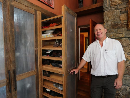 Architect and builder Sylvain Cote shows off the pull out shoe cabinet in the master bedroom of this South Salem Beach House on Truesdale Lake. The home was built using recycled materials.