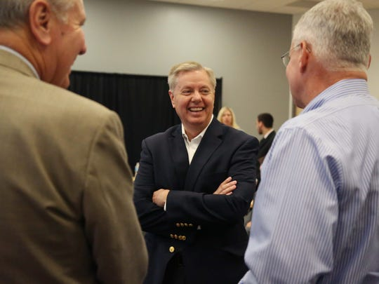 In this 2015 file photo, then presidential hopeful Sen. Lindsey Graham speaks to Rob Denson, left, of Des Moines Area Community College and David Caris of MidAmerican Energy at the Des Moines Register.