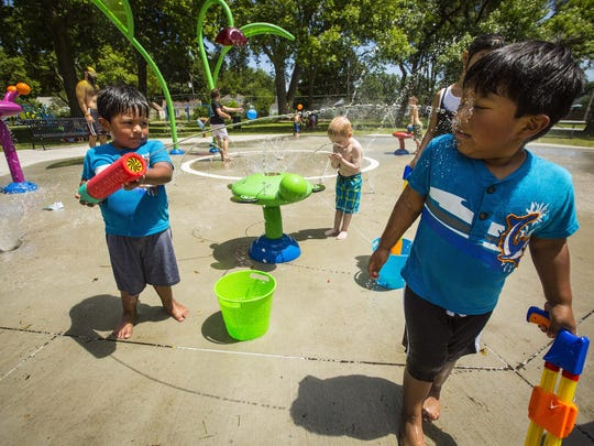 Jose Ramirez, 3, left, squirts his brother Jouse, right, in the wading pool at West Des Moines' Legion Park as hot weather bakes central Iowa Monday July 13, 2015.