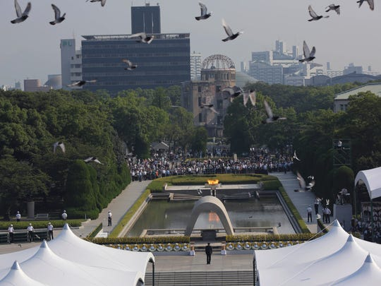 Doves fly over the cenotaph dedicated to the victims of the atomic bombing at the Hiroshima Peace Memorial Park during the ceremony to mark the 70th anniversary of the bombing in Hiroshima, western Japan Thursday, Aug. 6, 2015.
