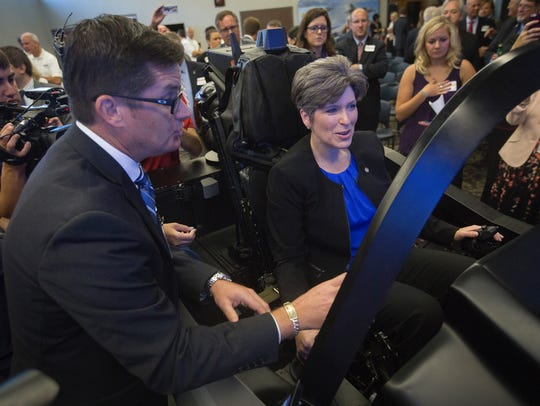 Sen. Joni Ernst tests out an F-35 Lightning II cockpit simulator with help from Matthew Cliver while visiting Rockwell Collins during a presentation of the company's F-35 helmet and heads up display in Cedar Rapids, Iowa, Tuesday, Aug. 11, 2015.