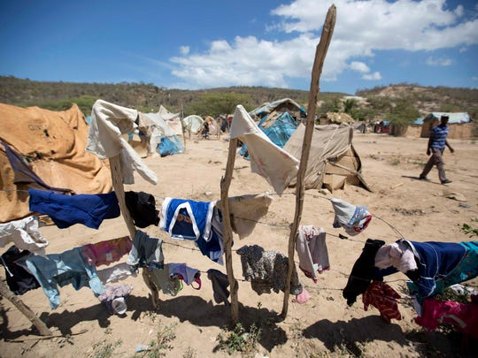 Clothes hang to dry in a camp set up by Haitians who