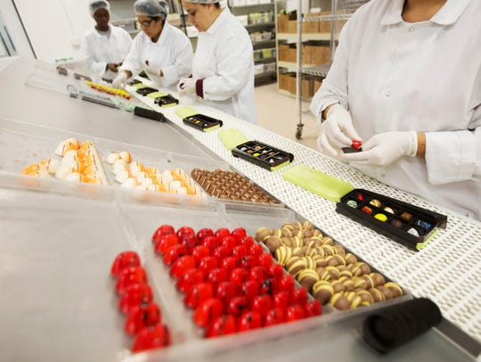 Workers box truffles at Norman Love Confections in
