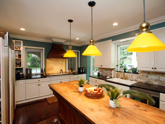 The kitchen cabinets in a New Rochelle Georgian are recycled from a company called Green Demolitions. The island was once a bar.