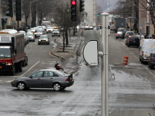 A pole-mounted red light camera watches traffic at