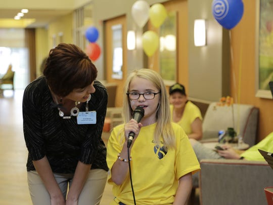 Kristin,11, sings Sunday, Sept. 27, 2015 to her father, Scott Bond, who has a terminal form of cancer. The Springs at Lafayette held a party for Bond after he and a team participated in the Carry the Torch walk, which raises money for Community Cancer Network.