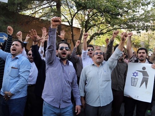 Iranian protesters shout slogans during a demonstration