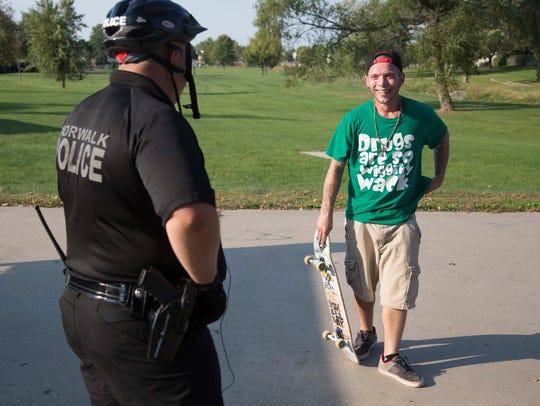 Norwalk officer Brad Criswell talks with Shawn Kreegy,