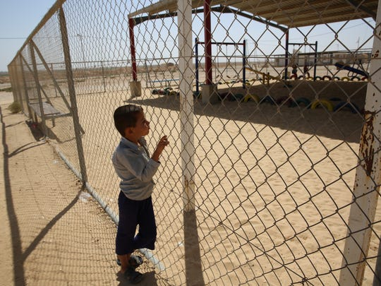 A child look in on a playground at the Zaatari Refugee Camp, the largest in the Middle East, home to nearly 80,000 Syrian refugees spread over 5,000 acres. Opened in July 2012, it contains trailers, schools, hospitals, shops and grocery stores.