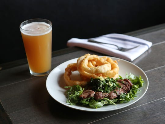 Venison flank steak with herb salsa verde and buttermilk onion rings at the Clock Tower Grill in Brewster.