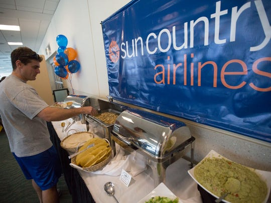 Ross Kravetz, a resident of North Fort Myers takes part in the free taco bar provided by Southwest Florida International Airport.  He was one of the first passengers on a Sun Country flight to Cancun.