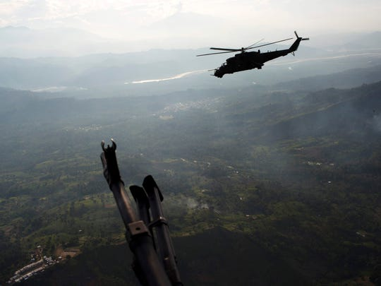 In this Sept. 19, 2014, file photo, a military attack helicopter flies over Pichari, Peru in the Apurimac, Ene and Mantaro river valley, or VRAEM. It is the world's No. 1 coca-growing region. Roughly half of Peru's cocaine exports have been ferried eastward, police say, since the rugged Andean nation became the world's leading producer of the drug in 2012. (AP Photo/Rodrigo Abd, File)