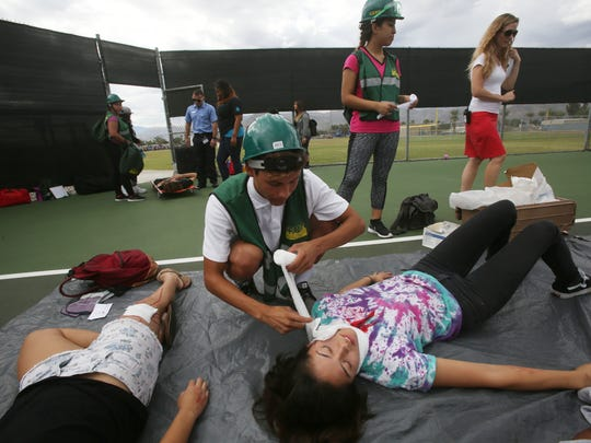 Cathedral City High School students from the Health and Environmental Health Academy of Learning participate in the Great Shake Out, which is an international earthquake drill that happens on October 15. In this photo student Roger Rodales attends to the pretend wounds of a fellow student.