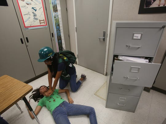 "Cathedral City High School students and staff participate in the Great Shake Out, which is an international earthquake drill that happens on October 15. Cathedral City High School also gave experience to their health academy students. In this photo a student playing the roll of ""search and rescue"" administers first aid to a student that play the role of an injured girl."
