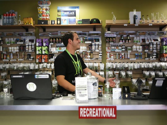 Ian Azzam, a bud tender at the Medicine Man marijuana dispensary and grow facility in Denver, works behind the counter. Unlike most Denver dispensaries, Ohio's medical marijuana dispensaries won't be open to the general public.