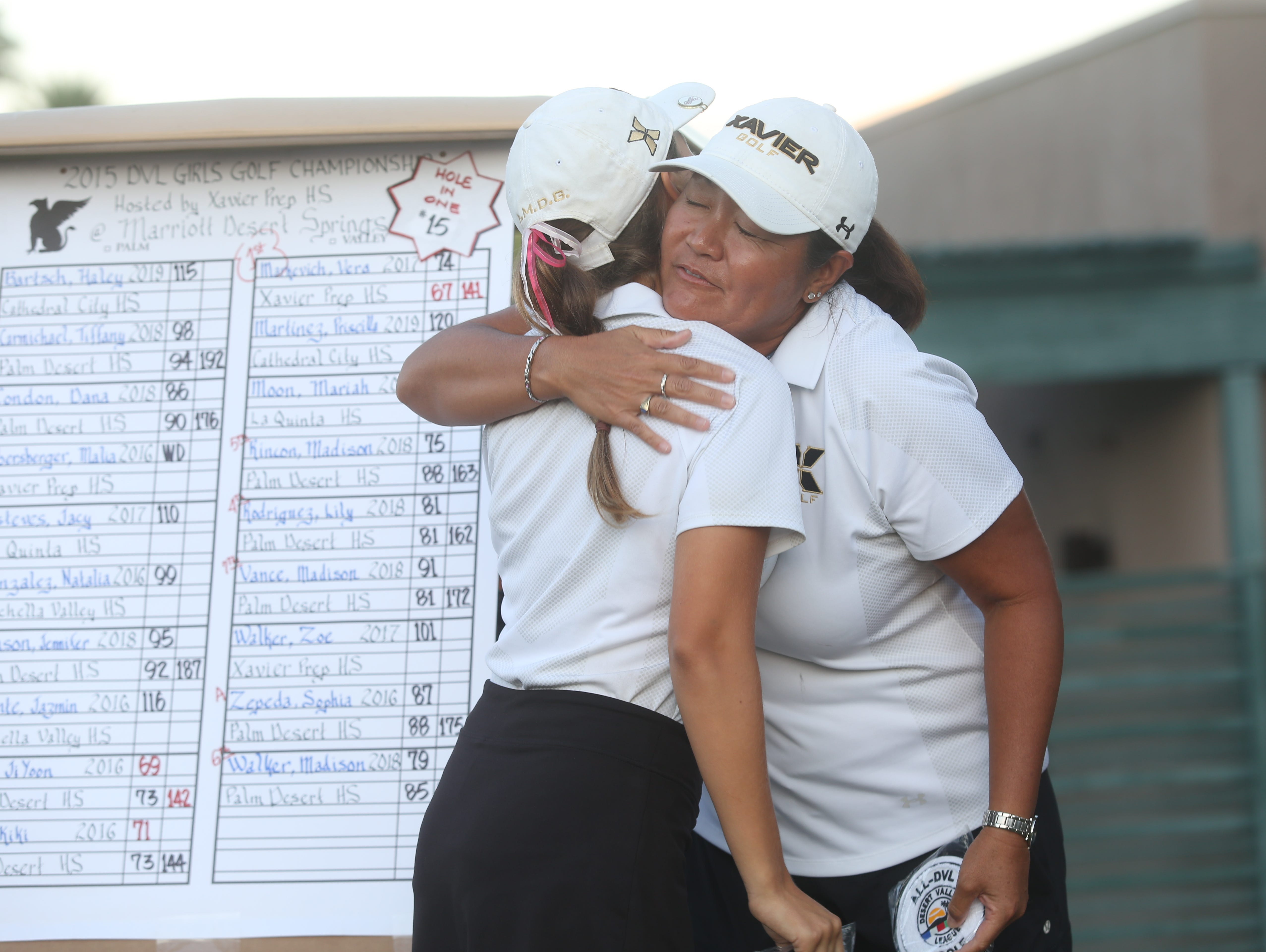 Vera Markevich, of Xavier Prep, gets a hug from her head coach Debbi Koyama after becoming the DVL champion in girls golf she won her round at Desert Springs Resort Marriot in Palm Desert on October 22, 2015.