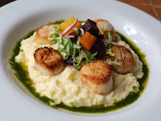 The Pan Seared scallops over goat cheese polenta, topped