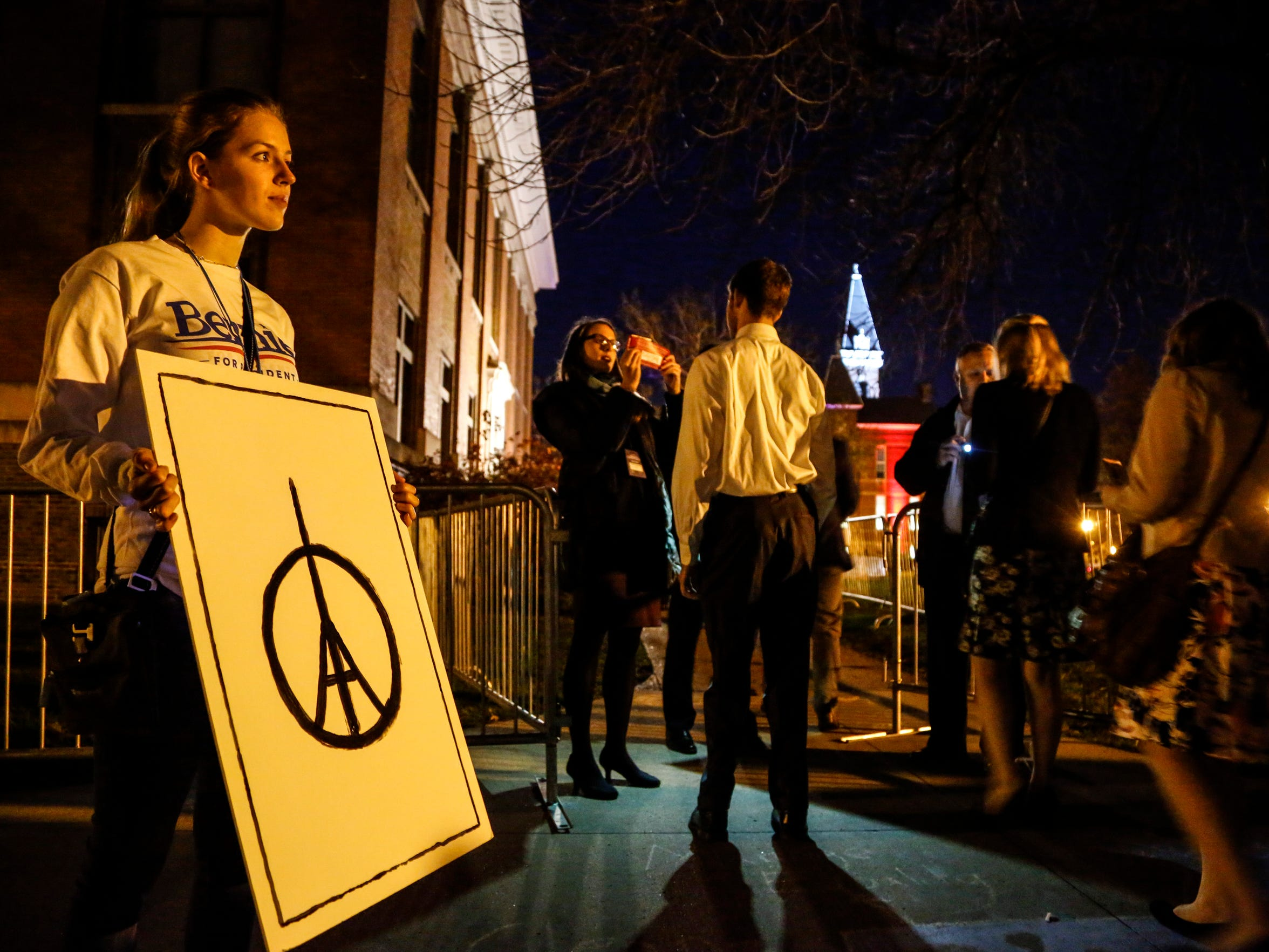 Paige McKibben of Des Moines holds a sign sending condolences to the people of Paris on the sidewalk outside Drake University before the debate Saturday, Nov. 14, 2015.
