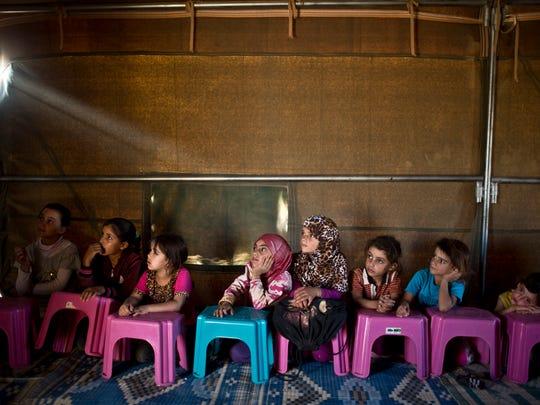 Syrian refugee children attend class at a makeshift