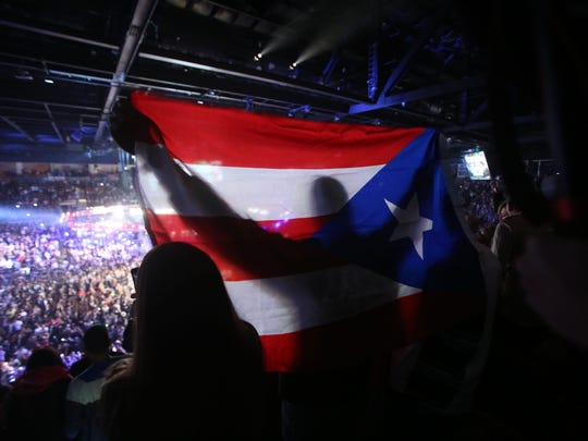 """Miguel Cotto fans cheer for their countryman during his fight against Mexico's Saul """"Canelo"""" Alvarez at the Mandalay Bay on November 21, 2015. Alvarez won the fight in 12 rounds."""