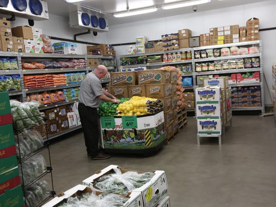 Store manager Joe Kirksey arranges bags of limes in the walk-in produce refrigerator at Cash & Carry's new store in South Salem on Dec. 7, 2015.