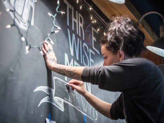 A Thr3e Wise Men staffer writes on a blackboard inside