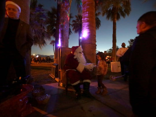 Children pose with Santa during the Indio Winter Festival on Saturday in old town Indio.