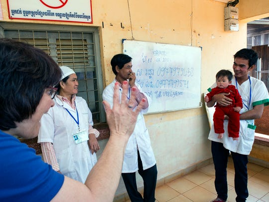 Kiwanis International President Sue Petrisin waves to a child who just got a checkup during her visit to a clinic in Cambodia in February.