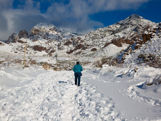 A woman walks though a snow-covered Soledad Canyon