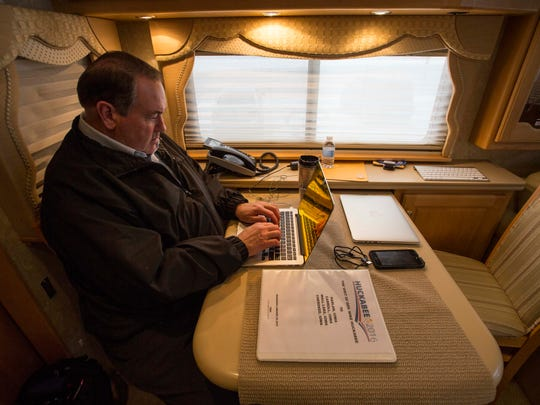 Republican presidential candidate Mike Huckabee works on his computer between  Harlan and Carroll, Iowa Wednesday Jan 20, 2016, on his RV.