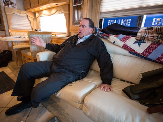Republican presidential candidate Mike Huckabee talks to a reporter on his RV between Harlan and Carroll, Iowa Wednesday Jan 20, 2016.
